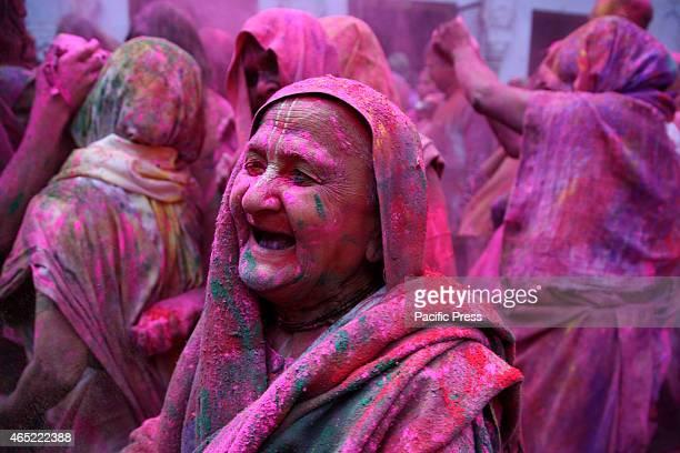 Hindu widows play colored powder as a part of Holi celebrations organized by the NGO Sulabh International at a Ashram in Vrindavan Holi is a spring...