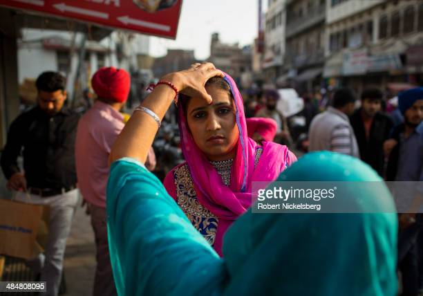 Hindu woman has a red bindi or sindoor applied by her mother February 23 2014 in Amritsar India