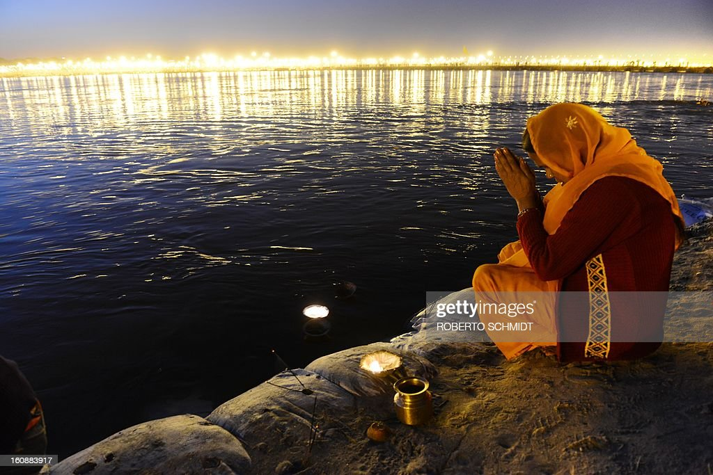 A Hindu woman prays on the shore of the confluence of the Yomuna and the Ganges river at the Sangam during the Maha Kumbh festival in Allahabad on February 7, 2013. The Kumbh Mela in the town of Allahabad will see up to 100 million worshippers gather over 55 days to take a ritual bath in the holy waters, believed to cleanse sins and bestow blessings.