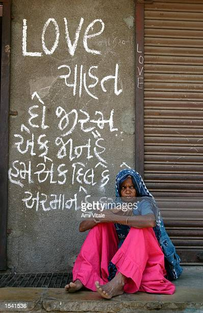 Hindu woman sits underneath graffitti written in Gujarati that reads 'LOVE Strength is in Unity' May 11 2002 in the state of Gujarat in Ahmedabad...