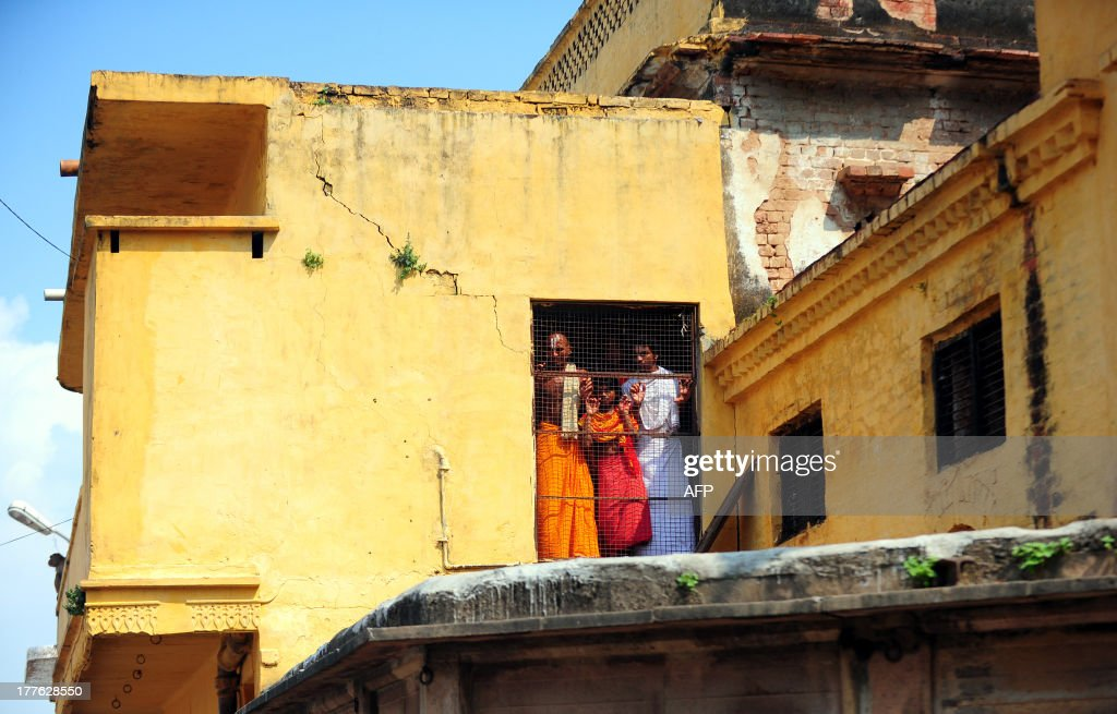 Hindu youth of the Veda Vidyalaya watch from a window as Indian soldiers patrol in Ayodhya on August 25, 2013. Indian police arrested leaders of a Hindu forum to try and prevent a march to a pilgrimage town where the 1992 razing of a mosque sparked deadly sectarian riots. Organisers from the Vishwa Hindu Parishad (VHP, World Hindu Council) and the Press Trust of India (PTI) said some 125 people were detained in the northern state of Uttar Pdaesh. AFP PHOTO/ SANJAY KANOJIA