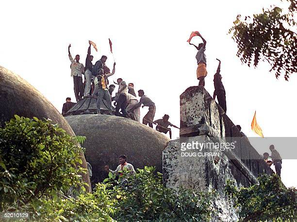 Hindu youths clamour atop the 16th century Muslim Babri Mosque in this 06 December 1992 file photo five hours before the structure was completely...