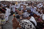 Hindus devotees pray during the Melasti ritual ceremony at Parangkusumo beach on March 28 2014 in Yogyakarta IndonesiaThe Melasti ritual is held...
