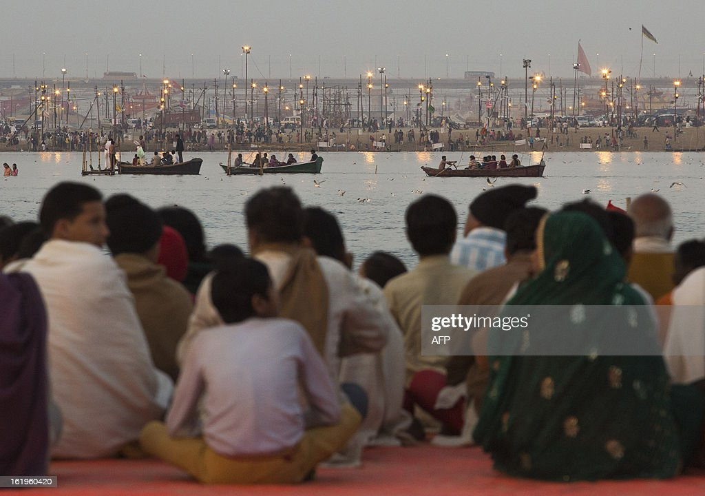 Hindus watch devotees bathing in the Sangam, the confluence of the Yamuna, Ganges and mythical Saraswati rivers during the Kumbh Mela in Allahabad on February 18, 2013. The Kumbh Mela in the town of Allahabad will see up to 100 million worshippers gather over 55 days to take a ritual bath in the holy waters, believed to cleanse sins and bestow blessings. AFP PHOTO/ Andrew Caballero-Reynolds