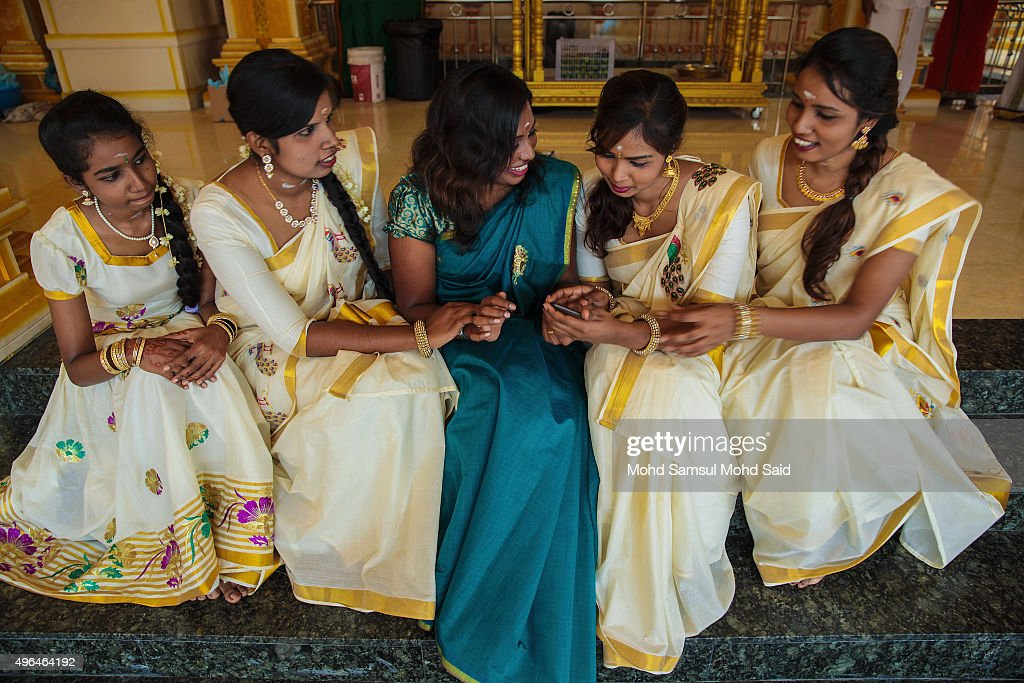 A Hindus women look their phone after take a photograph inside the temple during Diwali celebrations on November 10, 2015 in Shah Alam, Malaysia. The Hindu community, which consists of eight percent of Malaysia's population of 26 million, will celebrate Diwali, the festival of lights on November 10, known locally as Deepavali.