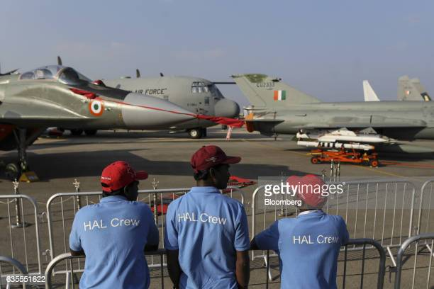 Hindustan Aeronautics Ltd workers stand near parked aircraft during the Aero India air show at Air Force Station Yelahanka in Bengaluru India on...
