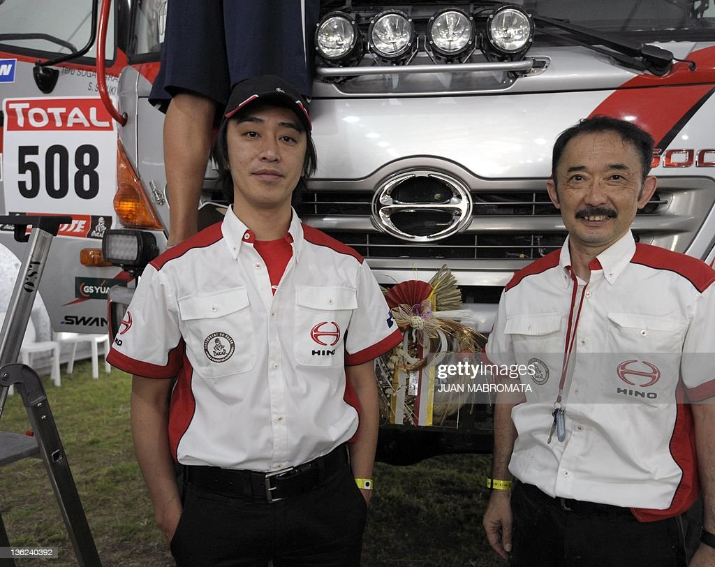 Hino truck driver Teruhito and codriver Seiichi Suzuki of Japan pose for a picture during the technical verifications of the Dakar 2012 in Mar del...