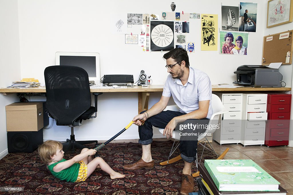 Hip father playing with toddler in home office : Stock Photo