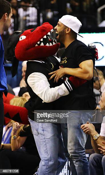 Hip Hop Artist Drake shares a laugh with the Raptor after a routine in which the Raptor dressed like Drake himself during their NBA game at the Air...