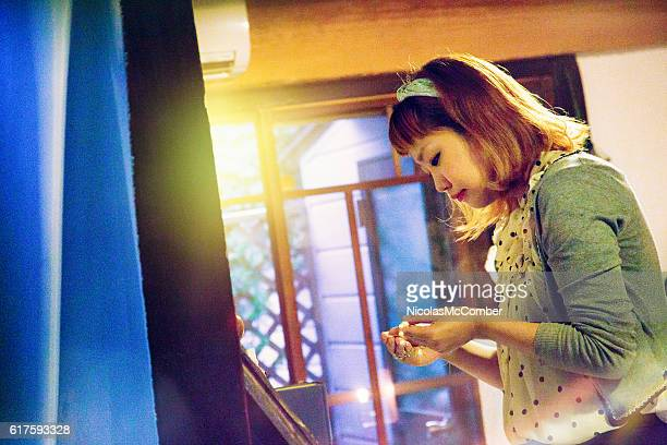 Hip Japanese female looking at jewelry in small shop