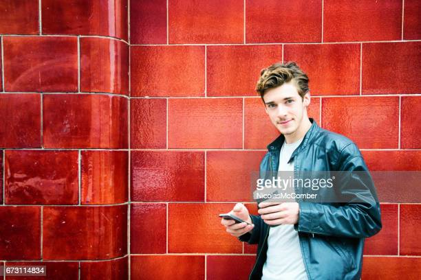 Hip millennial British man portrait against red wall with phone and coffee