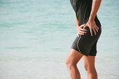 A male person at the beach, having severe hip pain, maybe due to an osteoarthritis. XXL size image.