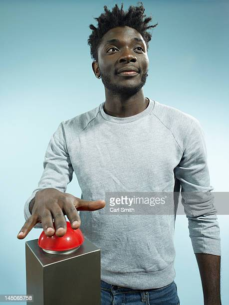 A hip young man with his hand poised above a red game show buzzer