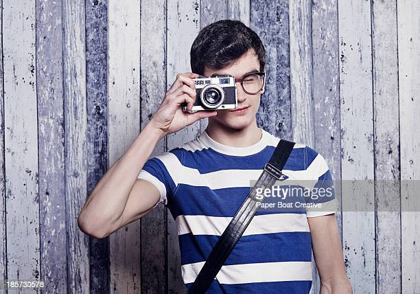 Hip young student taking a photo with film camera