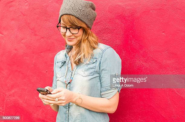 A hip young woman looking at smartphone smiling