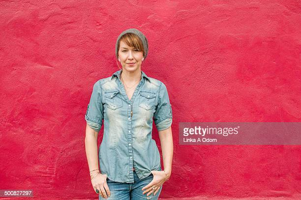 A hip young woman standing against a bright wall.