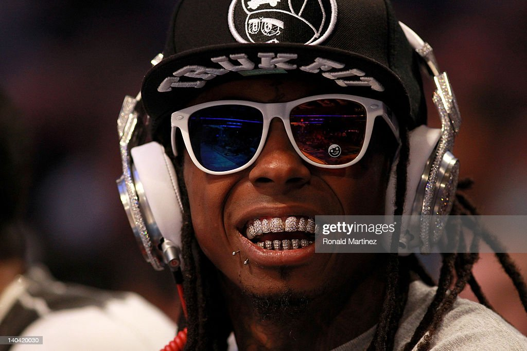 Hip-hop artist Lil' Wayne, wearing diamond studded beats headphones by Dr. Dre sits courtside during the 2012 NBA All-Star Game at the Amway Center on February 26, 2012 in Orlando, Florida.