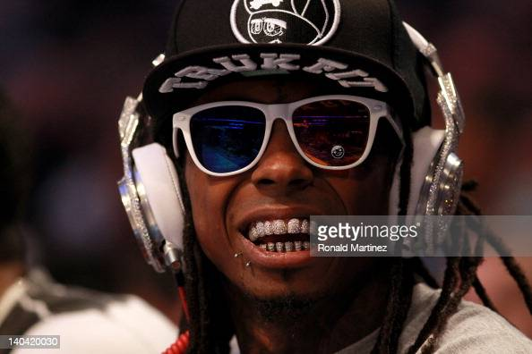 Hiphop artist Lil' Wayne wearing diamond studded beats headphones by Dr Dre sits courtside during the 2012 NBA AllStar Game at the Amway Center on...