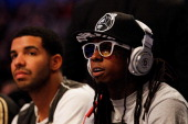 Hiphop artists Lil' Wayne wearing diamond studded beats headphones by Dr Dre and Drake sit courtside during the 2012 NBA AllStar Game at the Amway...