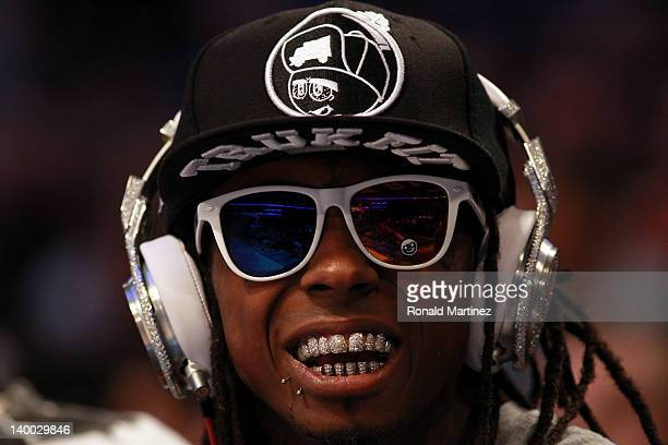 Hiphop artists Lil' Wayne wearing diamond studded beats headphones by Dr Dre sits courtside during the 2012 NBA AllStar Game at the Amway Center on...