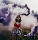 Hippie girl dancing in a park with purple smoke