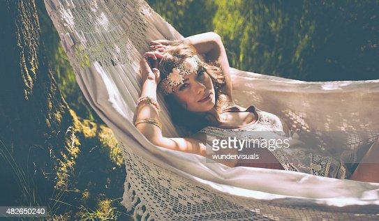Hippie girl relaxing in a hammock in a sunlit park