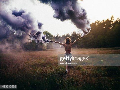 ヒッピー女の子を走るフィールドと、紫の煙で広がります。