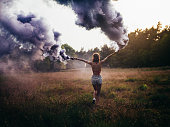 Hippie girl running through field with purple smoke flares