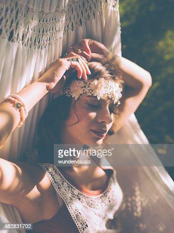 Hippie girl sleeping on a hammock in afternoon sun