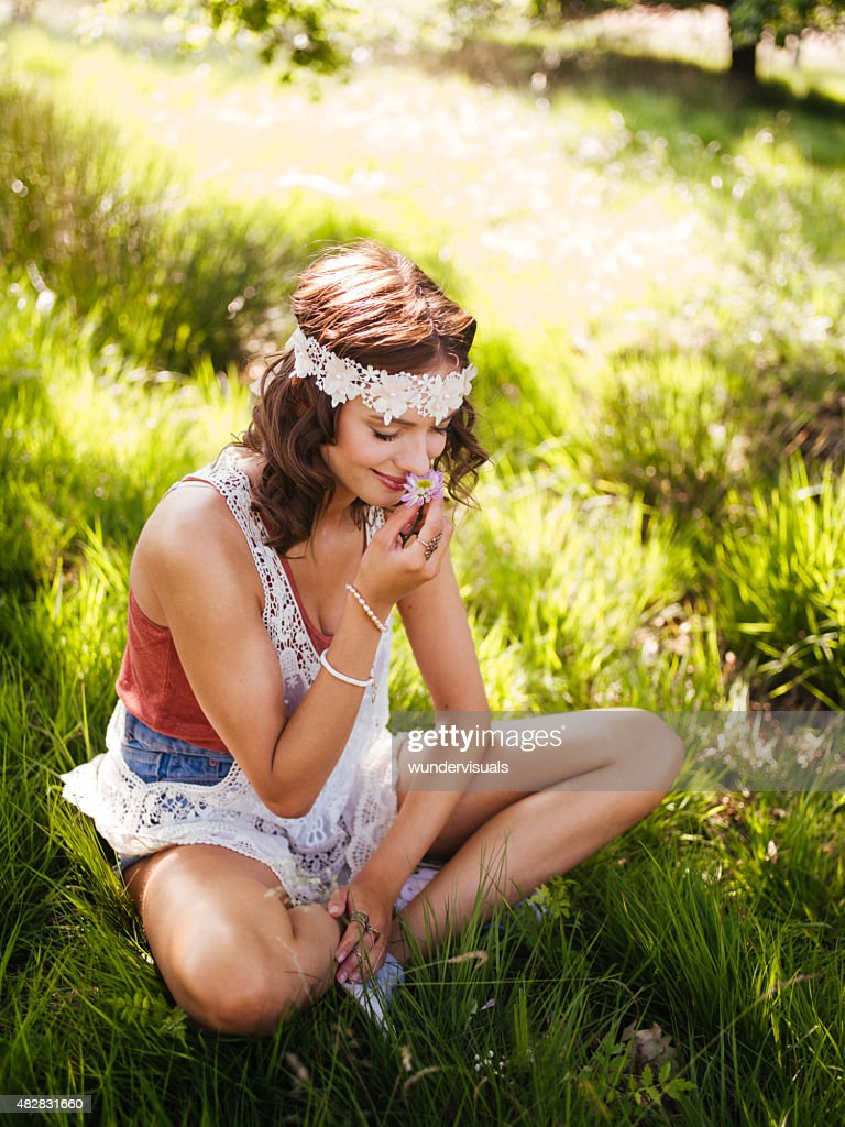 Hippie girl smelling a flower in a summer park : Stock Photo