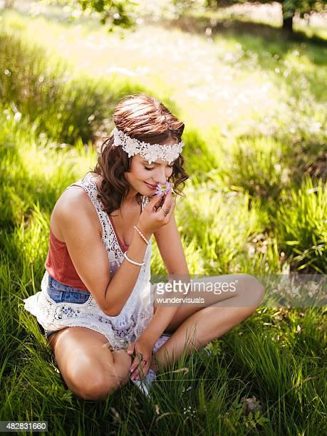 Hippie-Mädchen riechen Eine Blume in einem Sommer-park
