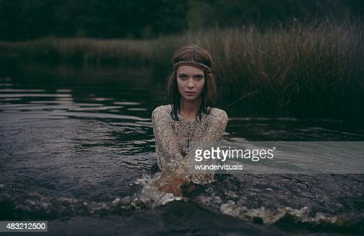 Hippie girl standing in a lake wearing a lace dress