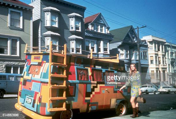 A hippie girl stands next to a Volkswagen bus painted in a bold design San Francisco California July 1967