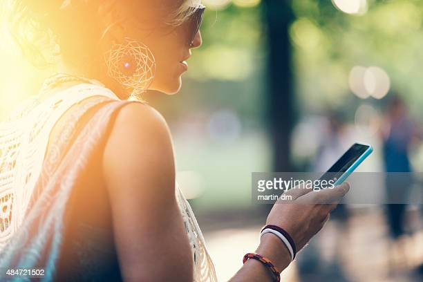 Hippie girl texting on smartphone outside