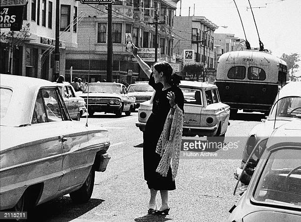 A hippie holding up a pamplet beside passing cars in the street San Francisco California c 1967
