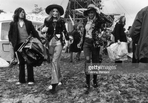 Hippie music fans walking through the mud at Bardney Pop Festival 9th June 1972 Both the women wear jeans floral jackets and wide brimmed hats