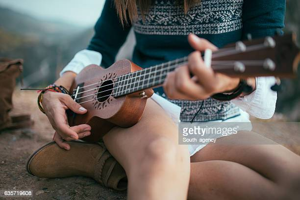 Hippie playing ukulele on top of the mountain