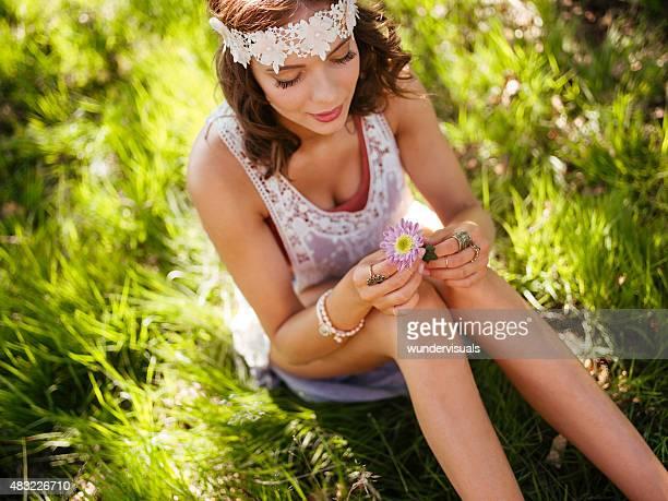 Hippie teenager holding flower in a summer park