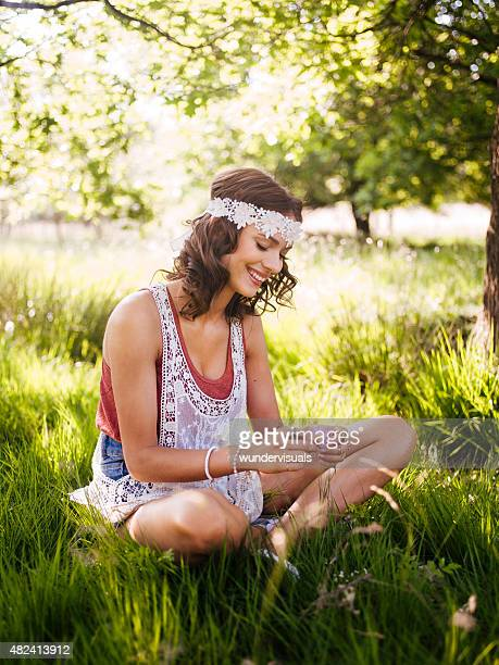 Hippie teenager sitting in a summer park loving nature