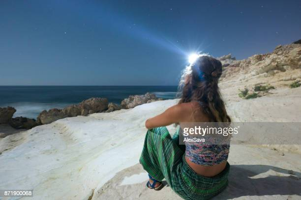 Hippie woman standing on the seashore at night