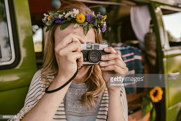 Hippie woman taking picture with analog camera in front of van