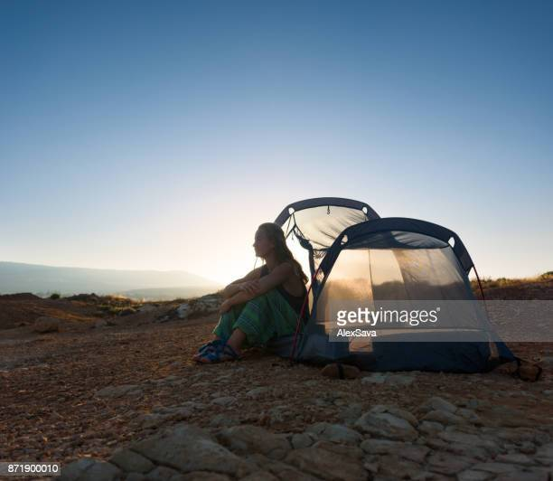 Hippie young woman camped on solitary beach in Paphos, Cyprus