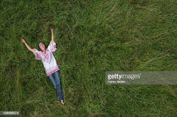 Hippy female relaxing in field