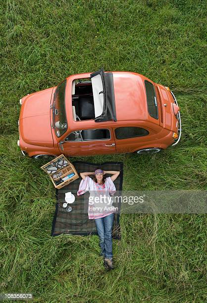 Hippy female relaxing with picnic by car