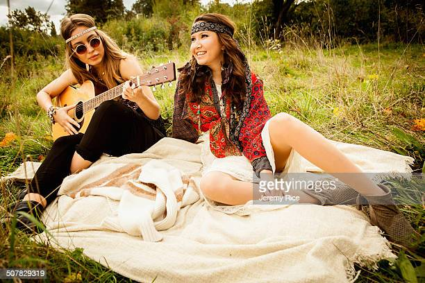Hippy girls on blanket in field, playing guitar