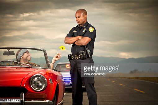 Hippy handing flower to a police officer : Stock Photo