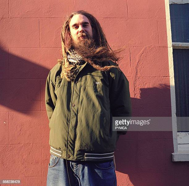 A Hippy man with a long beard and a dreadlocks standing against a wall Shoreditch London 2002