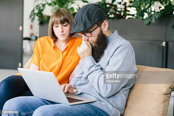 hipster and girlfriend sit on couch and work at laptop