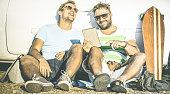 Hipster best friends having fun with tablet at car trip moment - Modern friendship and technology concept with always connected young people at alternative travel experience - Retro contrast filter
