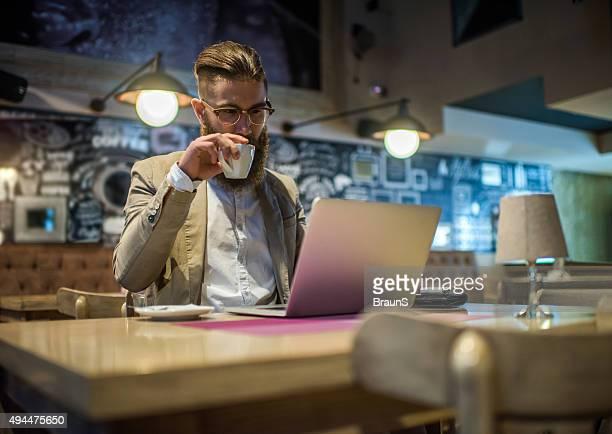 Hipster Geschäftsmann in einem Café Arbeiten auf laptop.
